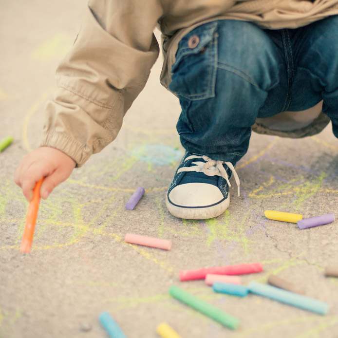 Child drawing on the street with coloured chalk