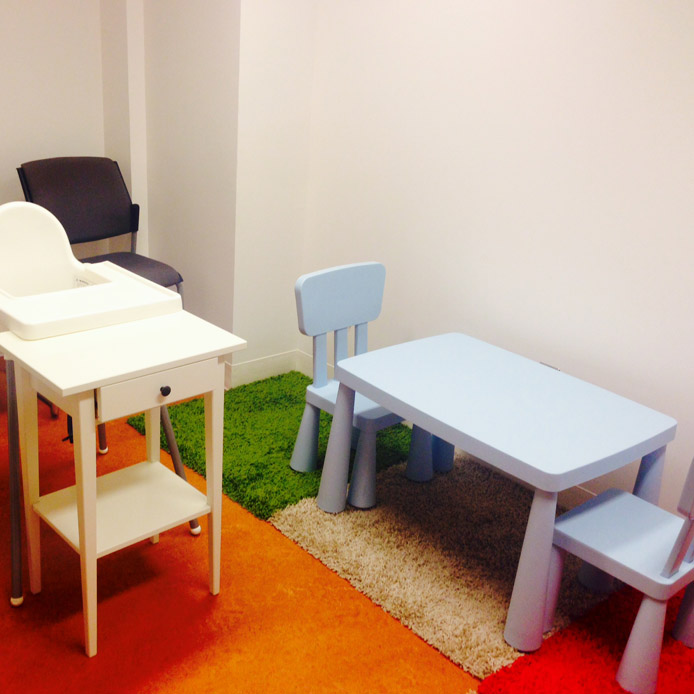 Room with a blue children desk and two matching blue chairs, a black chair, a white highchair and coloured carpeting.