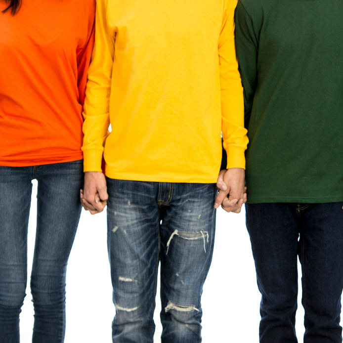 Group of people wearing brightly coloured shirts holding hands