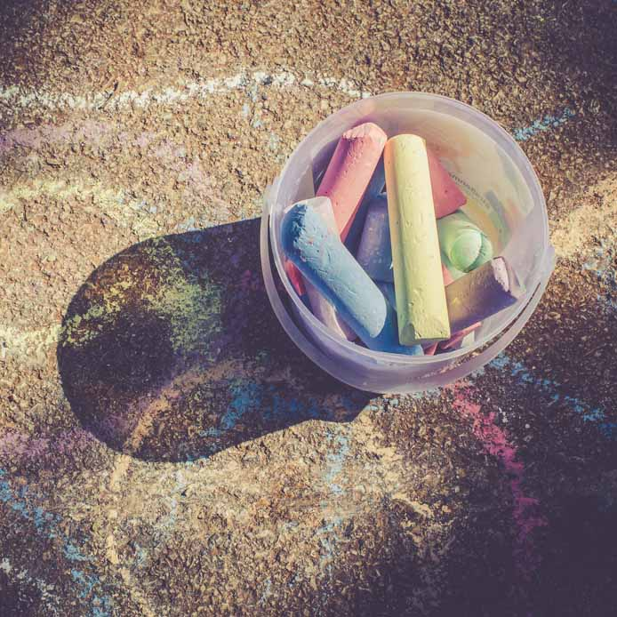 Coloured chalks in a plastic bin