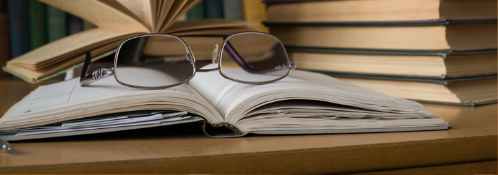 stacks of books on the side, with glasses placed on an open book in the centre