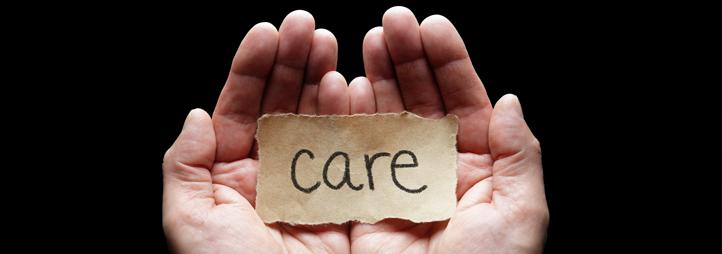 Le mot « care » sur un morceau de papier brun, dans une paume de main