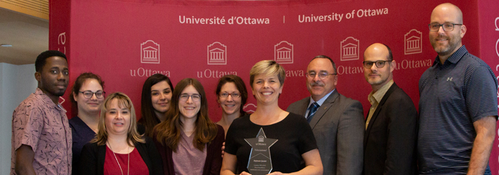 Professor Stéphanie Gaudet holding her award, surrounded by people.
