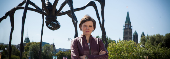 "Andrea Ashbaugh standing in front of ""Maman"" a large black spider sculpture with the Parliament buidlings in the background"