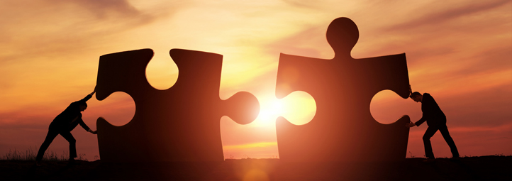 two men each pushing a giant puzzle piece together in front of sunset