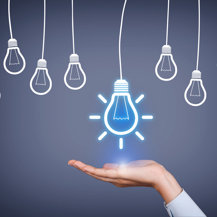 Open hand facing up with an illuminated lightbulb above it. Five smaller lightbulbs hang down around it.