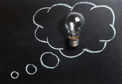 Une ampoule sur fond noir entouré de bulles de texte blanches. L'image est une représentation abstraite de cours de recherche qui suscitent la réflexion.