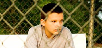Boy behind a fence