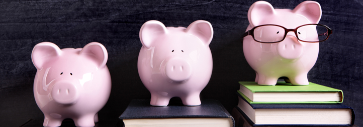 3 piggy banks on a row of books