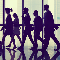 business men and woman walking towards something