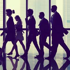 business men and woman walking towards something