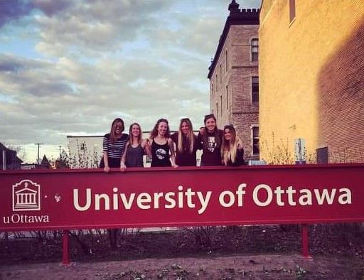Janine and her 5 roommates locking arms and smiling behind the University of Ottawa sign on a sunny day