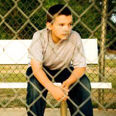 Boy sits behind a fence
