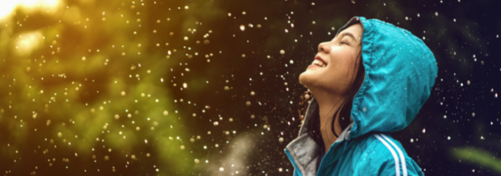 young woman in turquoise rain coat smiling under showers