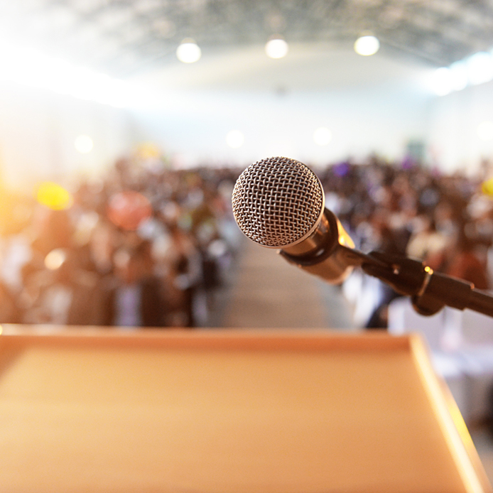 Podium with microphone in front of an audience