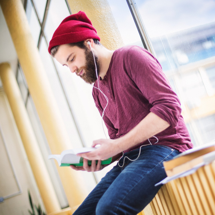Male caucasian student with red tuque on reading by window