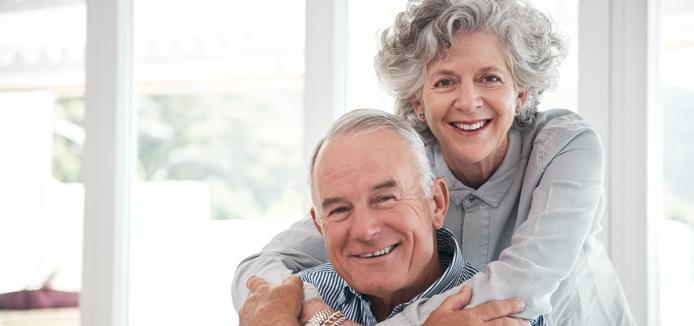 Elderly caucasian couple embracing with smiles.