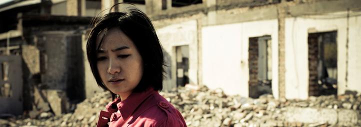 Asian woman standing in rubble