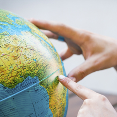 hand pointing to areas on the globe