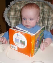 Baby in baby chair looking at book