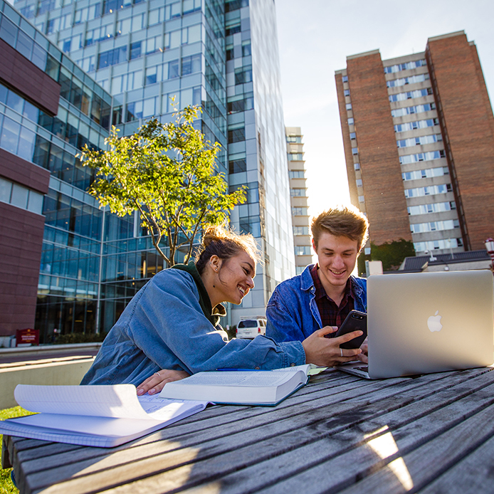 two students looking at a smartphone while studying outdoors in front of Faculty of Social Sciences Buidling