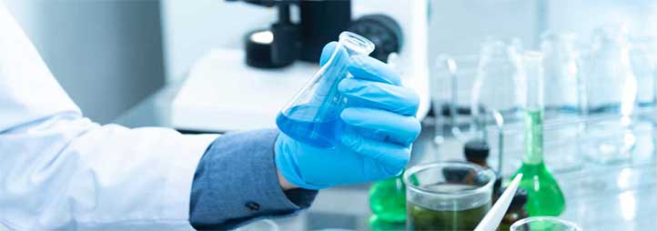 Picture showing a scientist's gloved hands manipulating a test tube in a laboratory