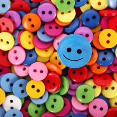 happy face button on top of multi coloured regular buttons