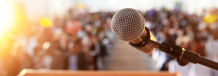 Microphone at a podium in front of a crowd