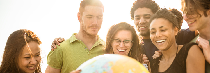 College students smiling holding a globe