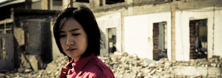 Woman standing in front of destroyed building