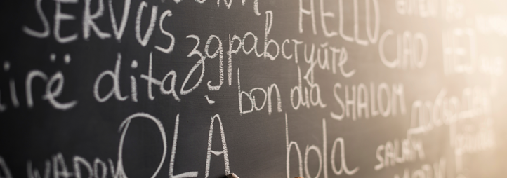 Word hello in different languages on blackboard