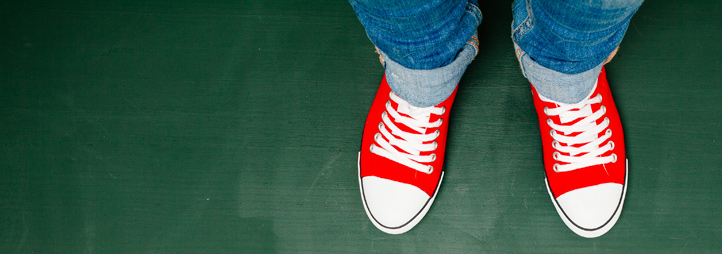 pair of red shoes standing on green chalkboard