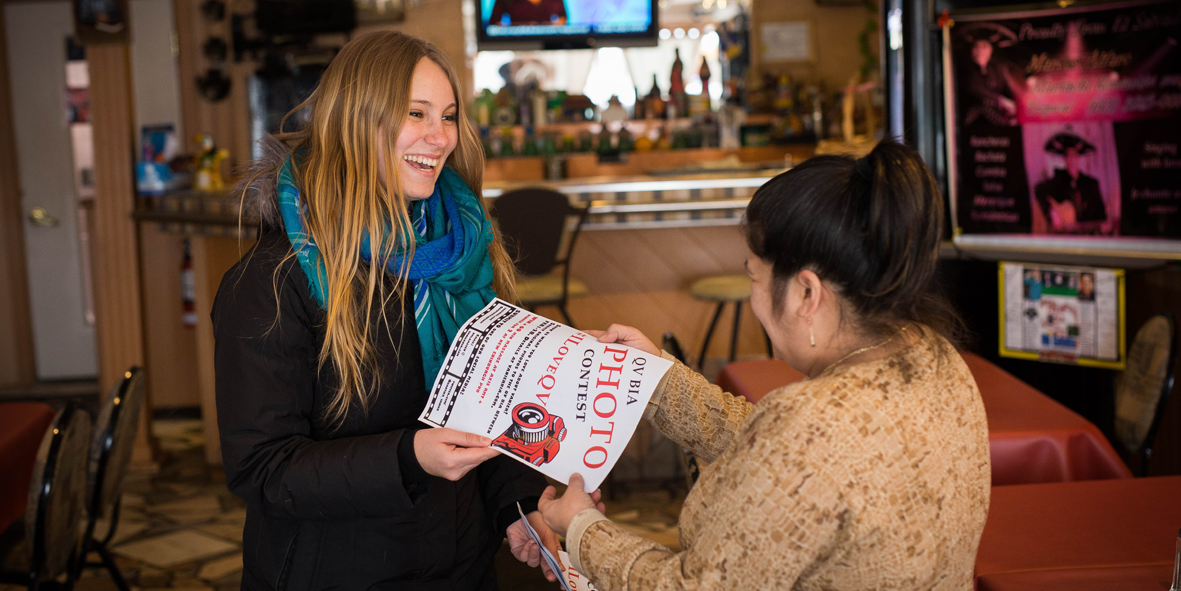 two women in a workplace holding a poster smiling