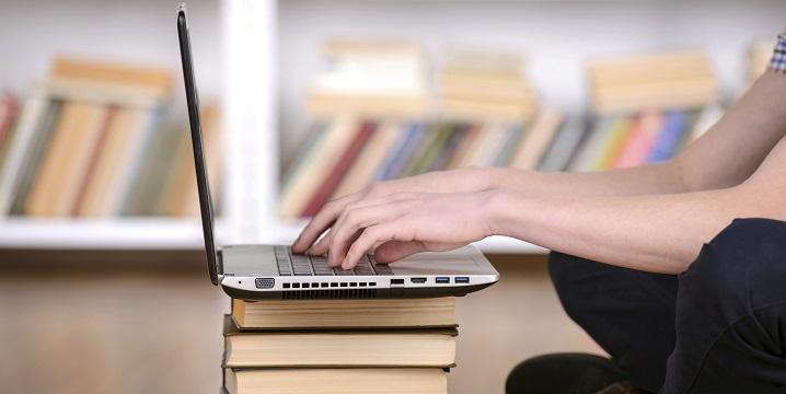 Main et laptop sur les livres