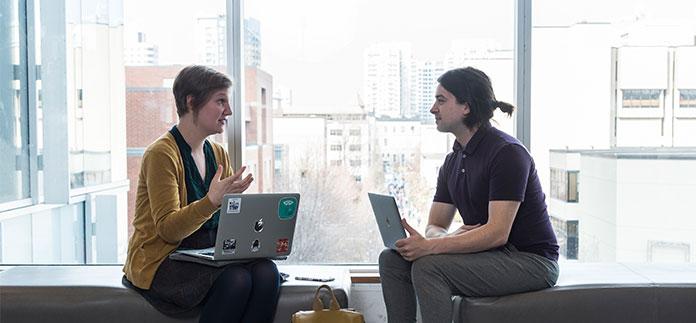 Deux étudinats avec leur ordinateur portable discutent chacuns sur leur banc