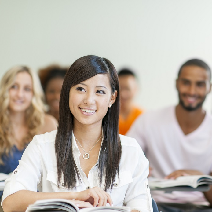 Smiling asian undergraduate student in class