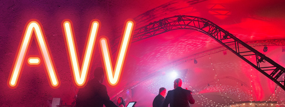 Alumni Week logo with the an A and W in neon and two people in the background.