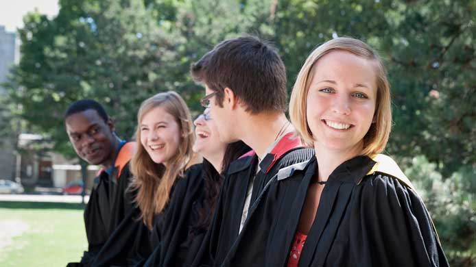 students laughing wearing graduation gowns