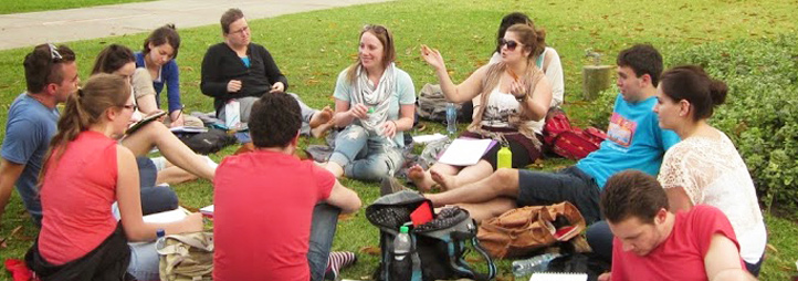 group of students sitting in a circle outside learning