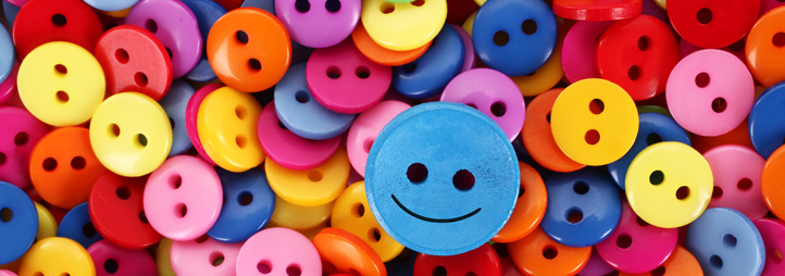 happy face button on top of multicoloured regular buttons