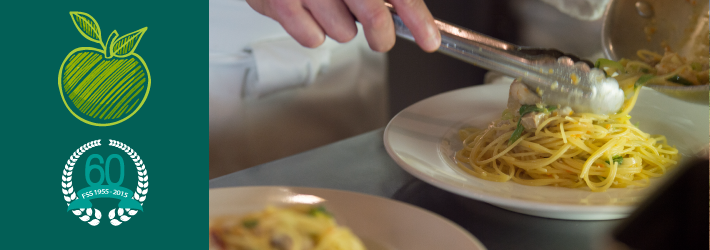 a hand plating pasta