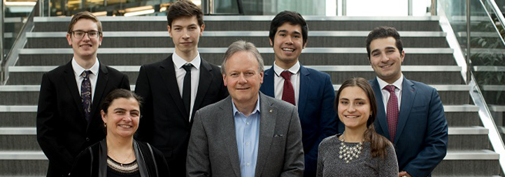 A group of people pose in front of a set of stairs.  The uOttawa Governor's Challenge team (from left): Nico Palesch, Faculty adviser Lilia Karnizova, James Bertram Foster, Bank of Canada Governor Stephen Poloz, Jaime Casigay, Diva Astinova, Raymond-Elia