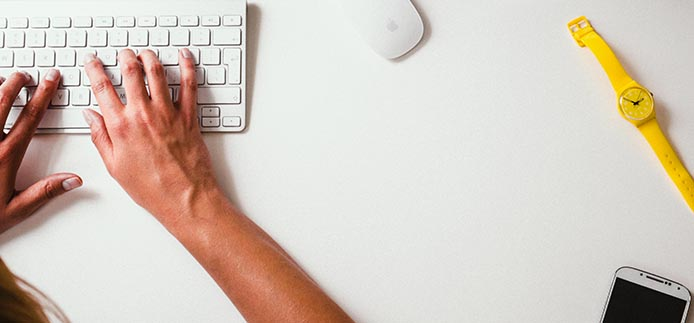 Two hands typing on keyboard. watch, mouse and iphone visible