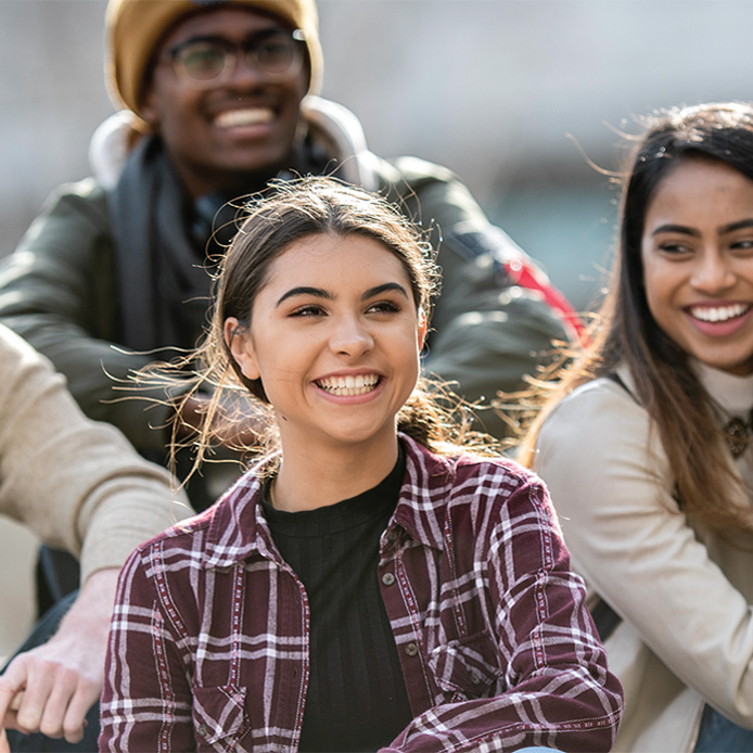 2 female and 1 male undergraduate students smiling outdoors