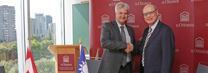 Handshake between Dean Marcel Mérette and representant Kung