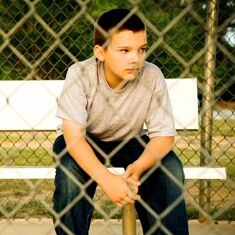 Boy sits behind a fence