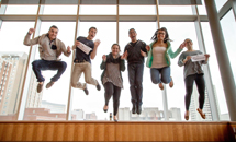 Students jumping in front of window.