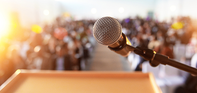 podium with microphone in front of a crowd