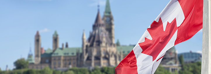 canadian flag waving with parliament buildings in background