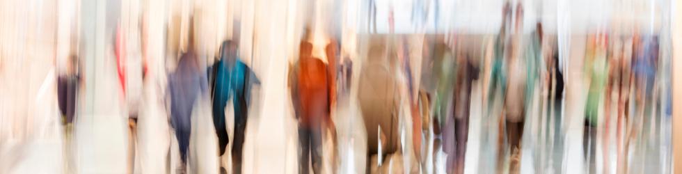 Blurred image of several people walking
